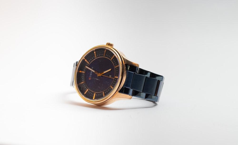 gold and black round analog watch