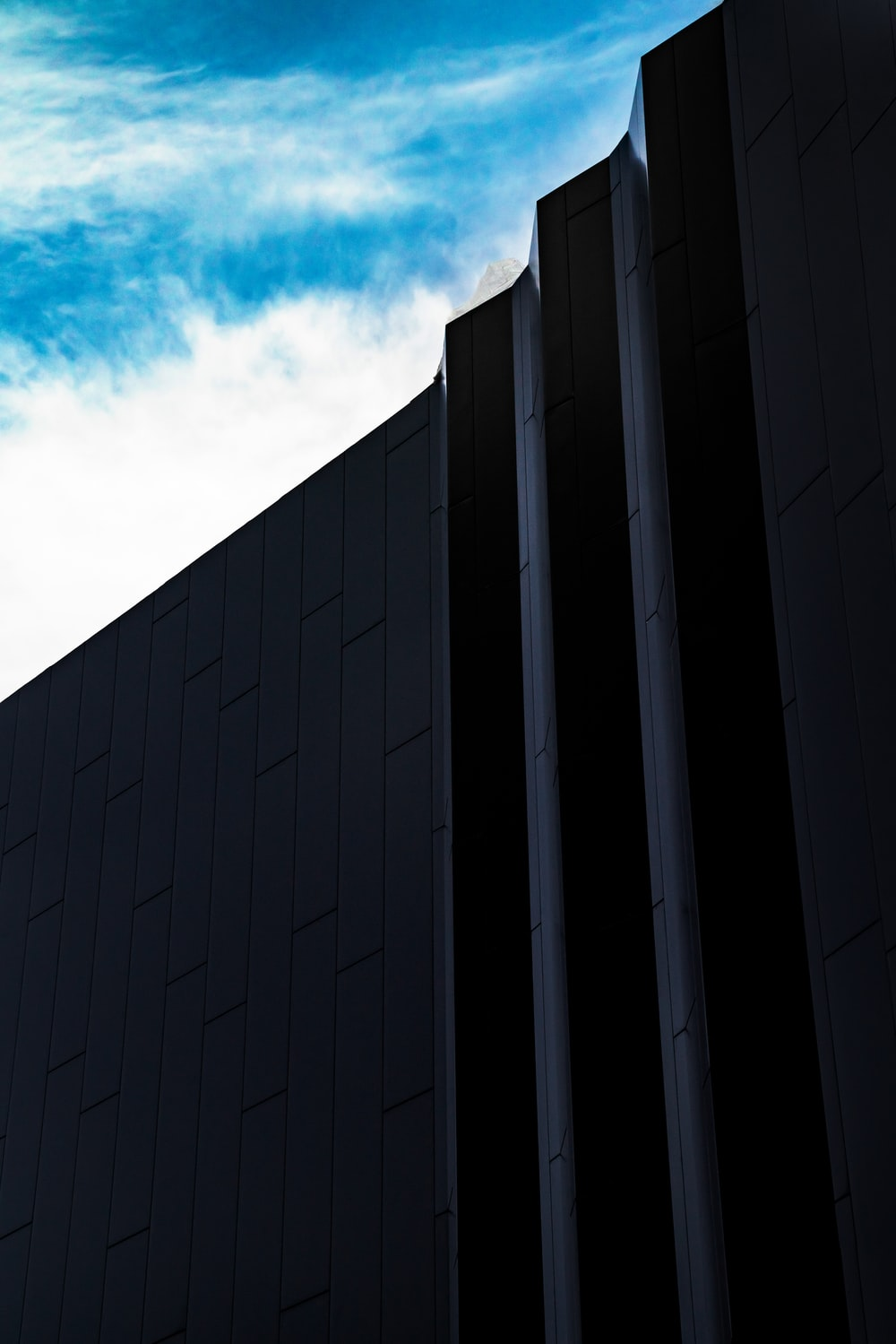 black concrete building under blue sky and white clouds during daytime