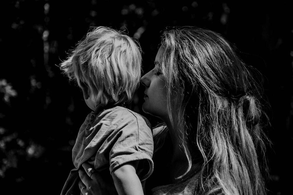grayscale photo of woman kissing boys cheek