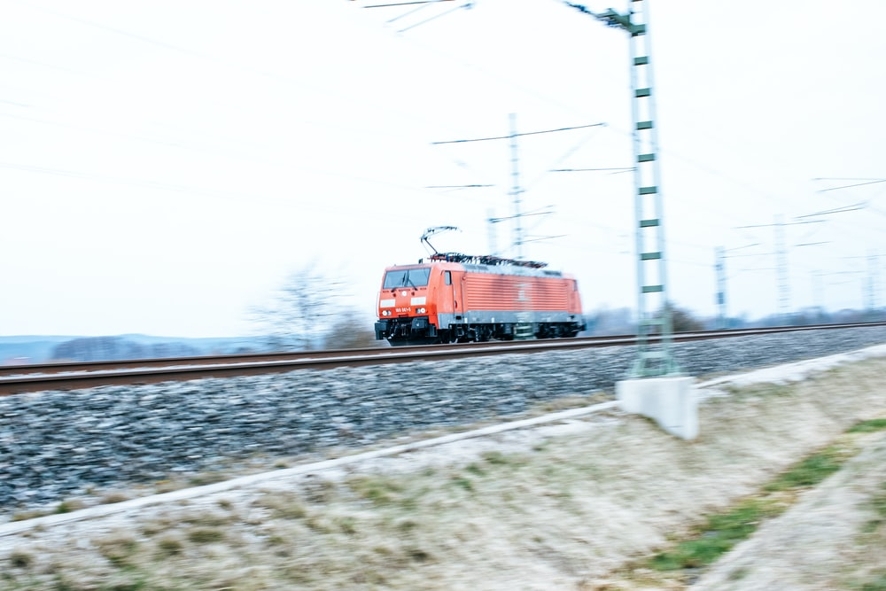 red and black train on rail tracks during daytime