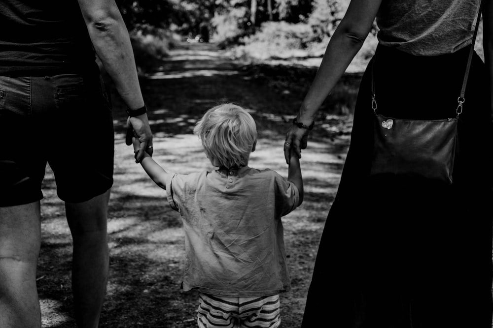 grayscale photo of woman in black dress holding child in black shirt