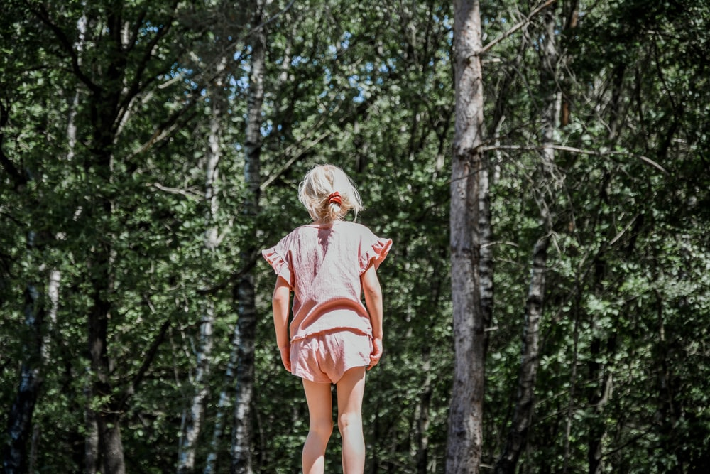 woman in orange and white stripe shirt standing in forest during daytime