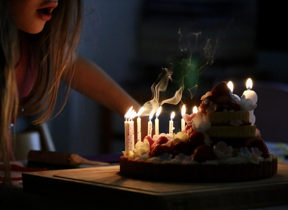 woman in white tank top holding lighted candles