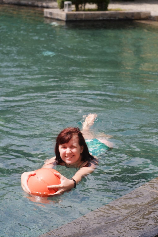woman in black bikini top on water holding orange inflatable ring