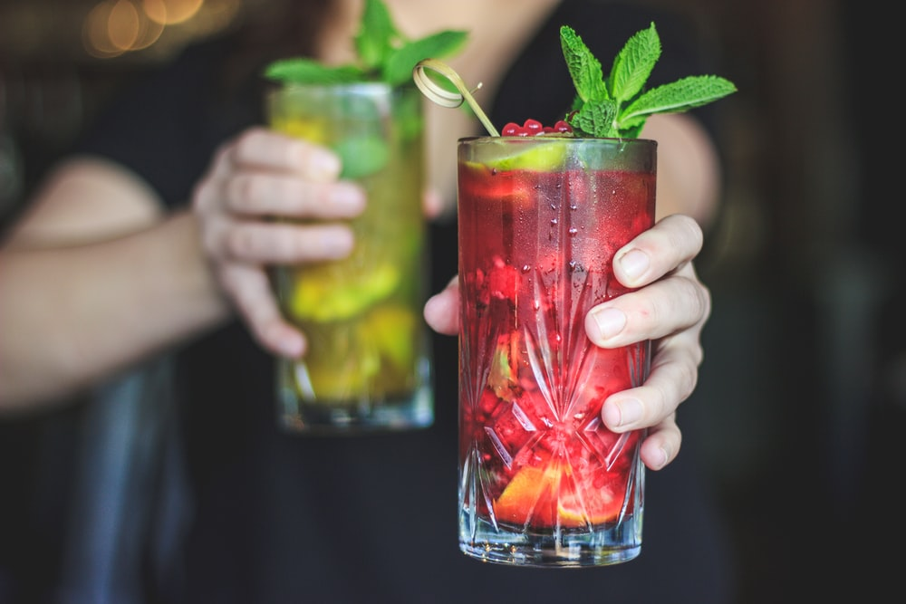 person holding clear drinking glass with red liquid and green leaves