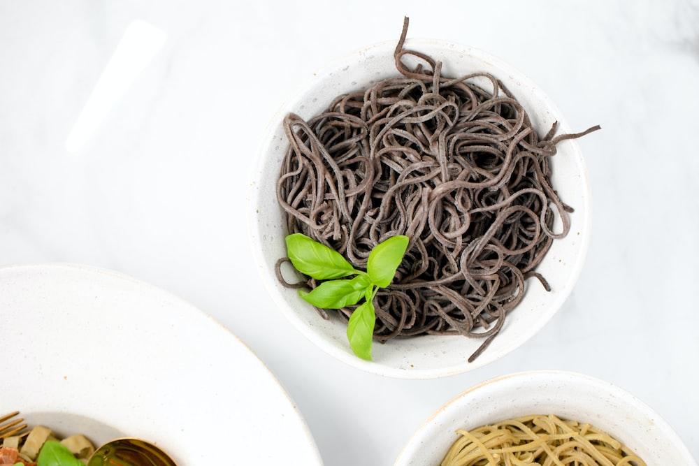 brown and white pasta on white ceramic bowl