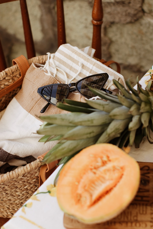 black framed sunglasses on brown woven basket