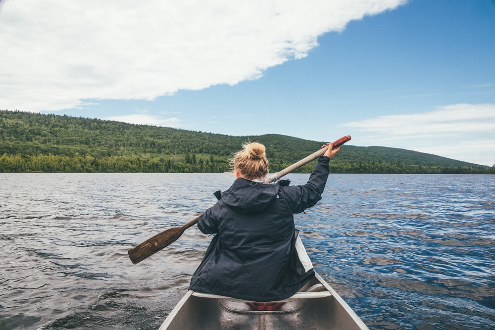 woman in black jacket riding on boat during daytime