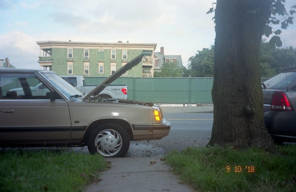 silver sedan parked on sidewalk during daytime