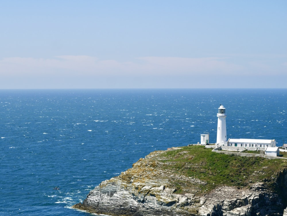 white lighthouse on cliff by the sea during daytime