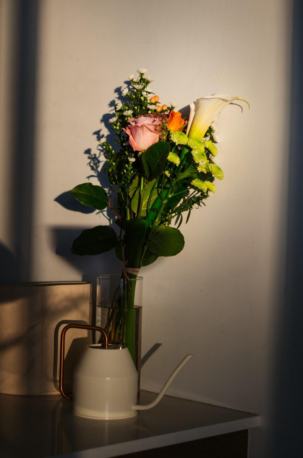 white and pink roses in white ceramic vase
