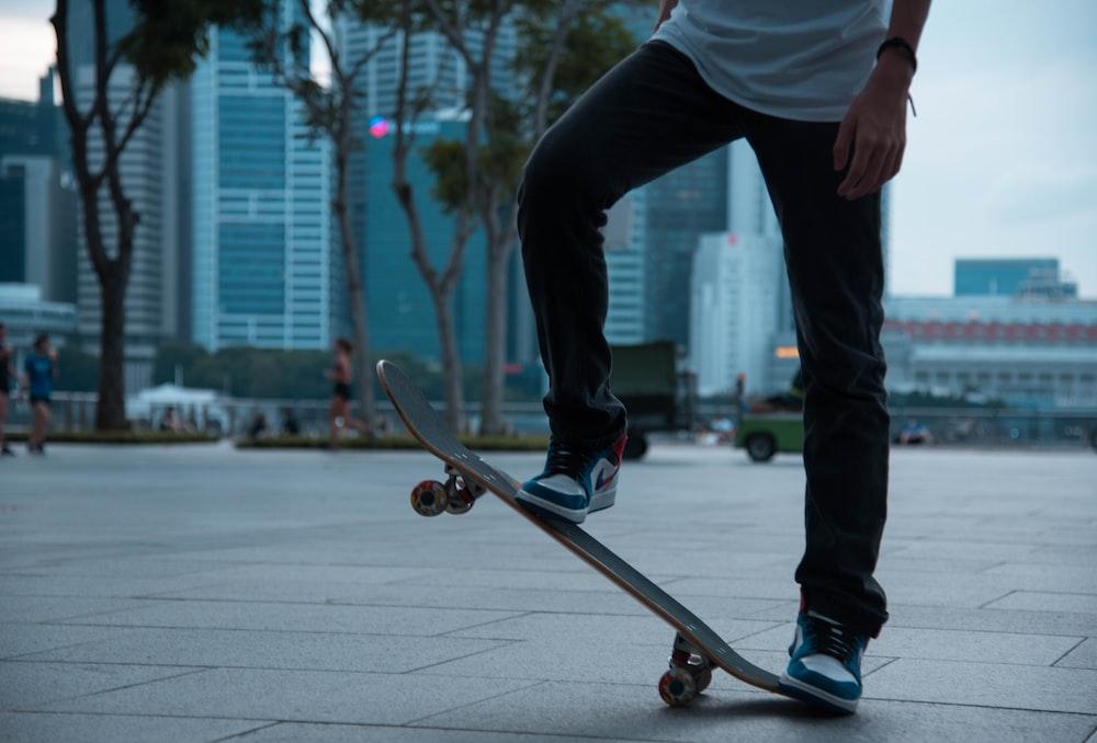 man in white shirt and black pants riding skateboard