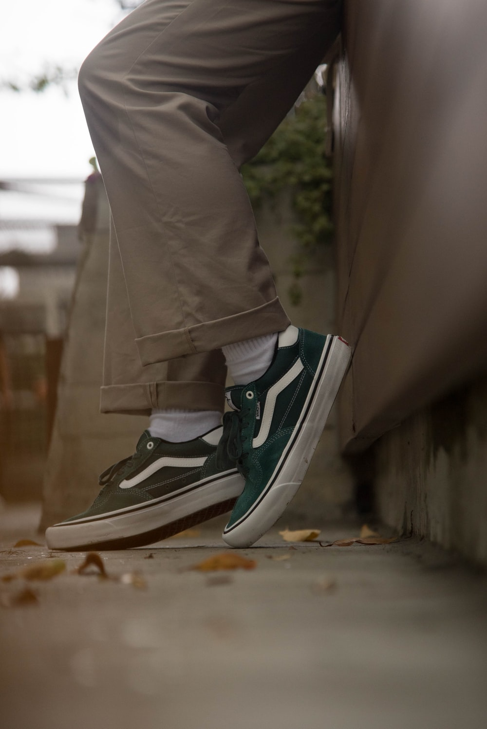person in gray pants wearing black and white nike sneakers