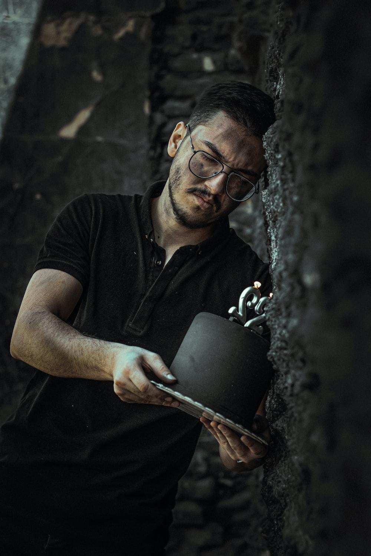 man in black polo shirt holding black ceramic mug