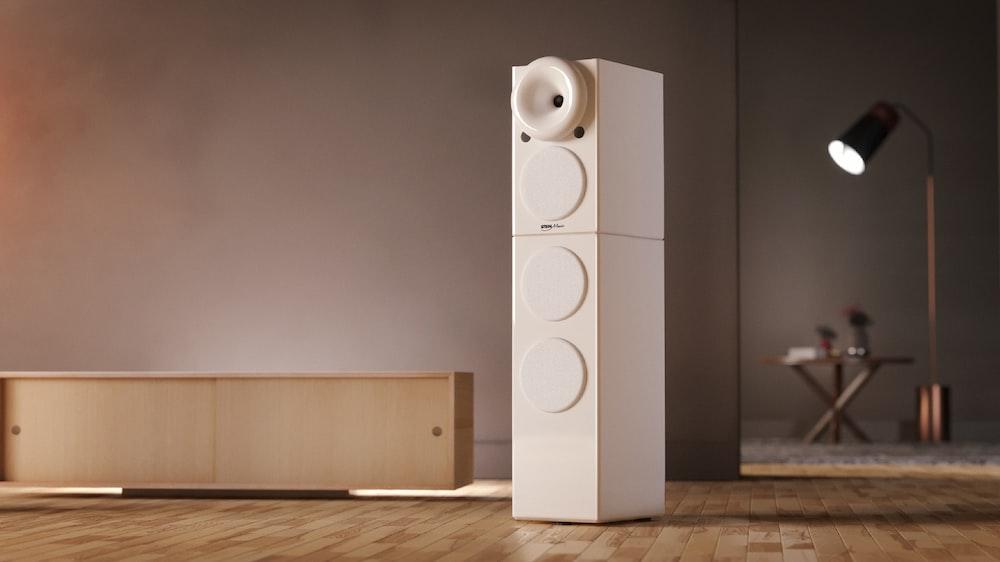 white speaker on brown wooden floor