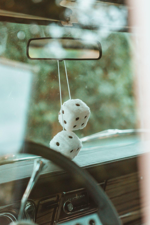 white and black plush toy on car rear mirror