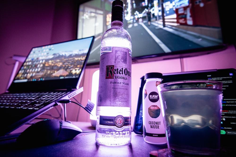 clear glass bottle beside clear drinking glass