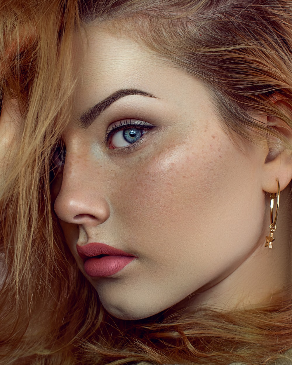 woman with brown hair wearing gold earrings