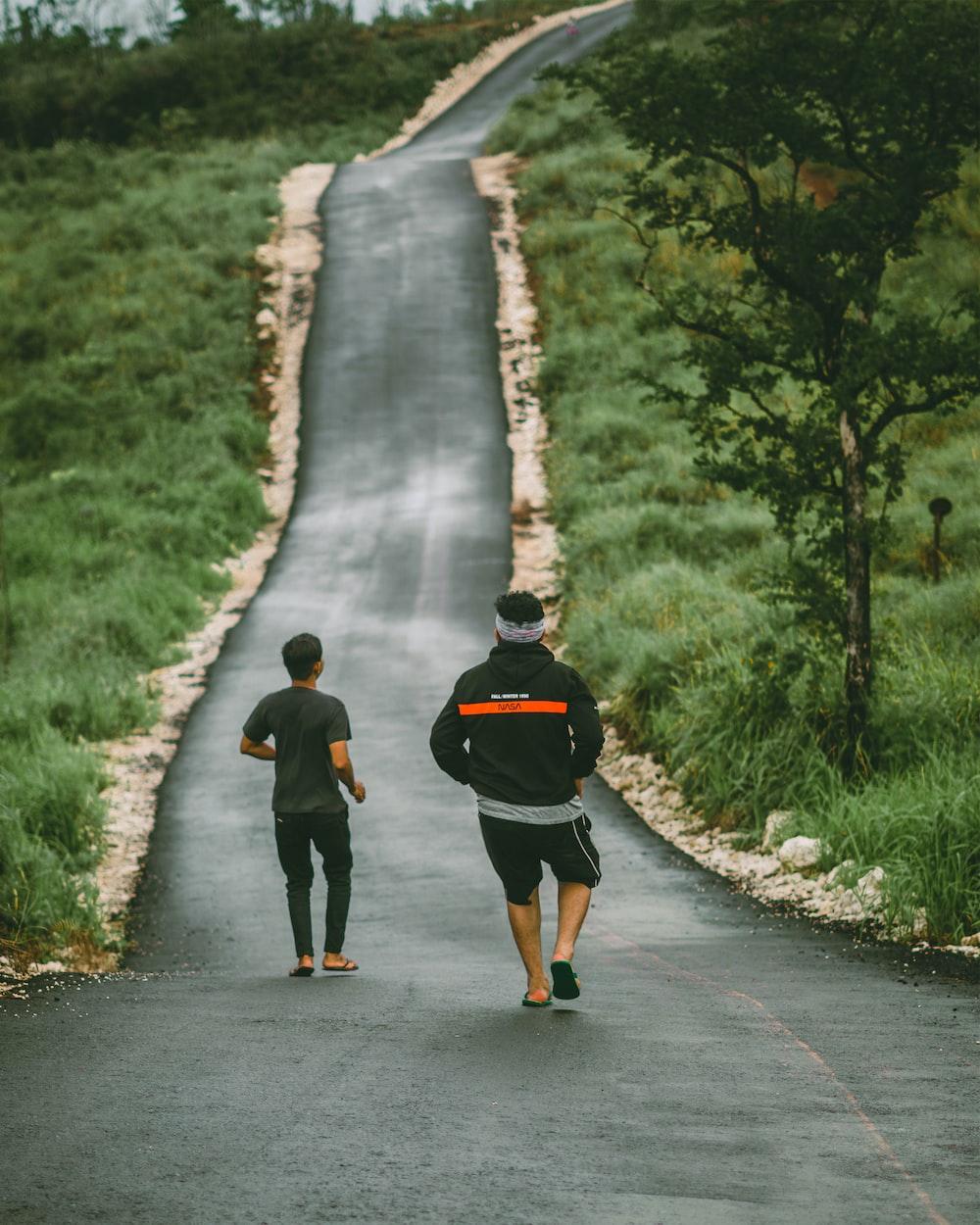 2 men walking on gray concrete road during daytime