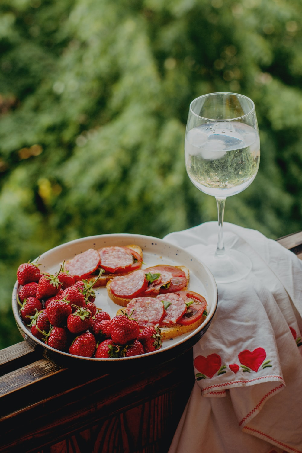 strawberries in bowl beside wine glass on table