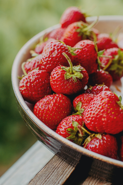 red strawberries in white ceramic bowl