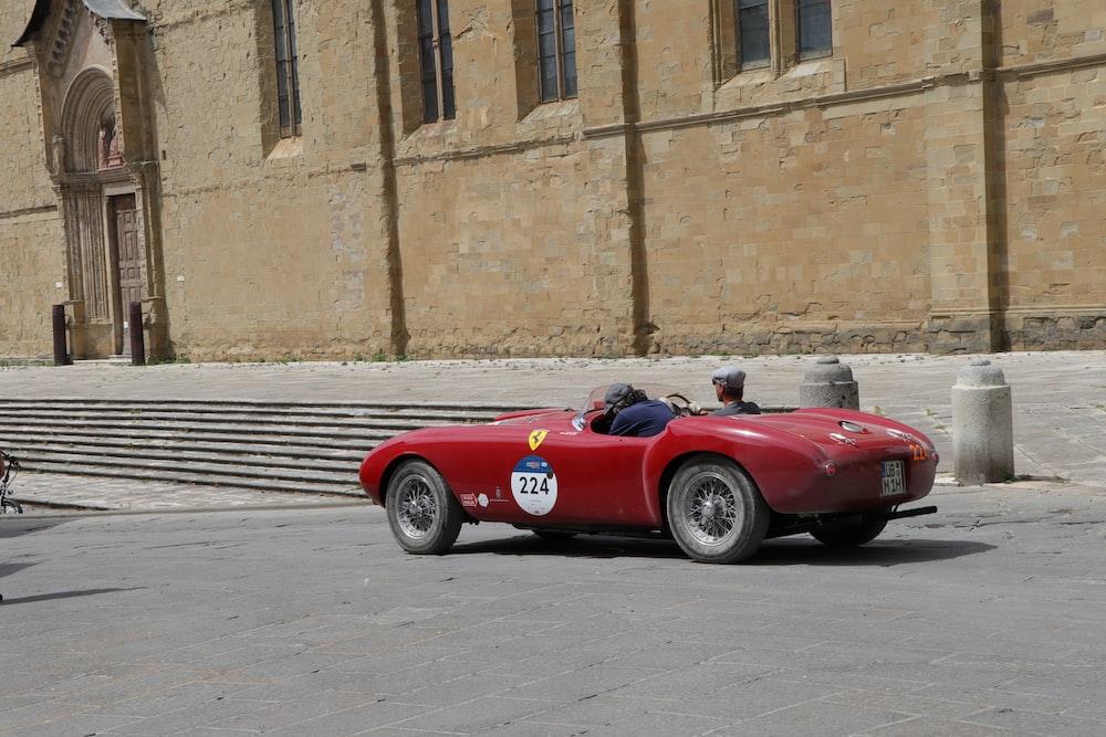 red ferrari 458 italia parked beside brown concrete building