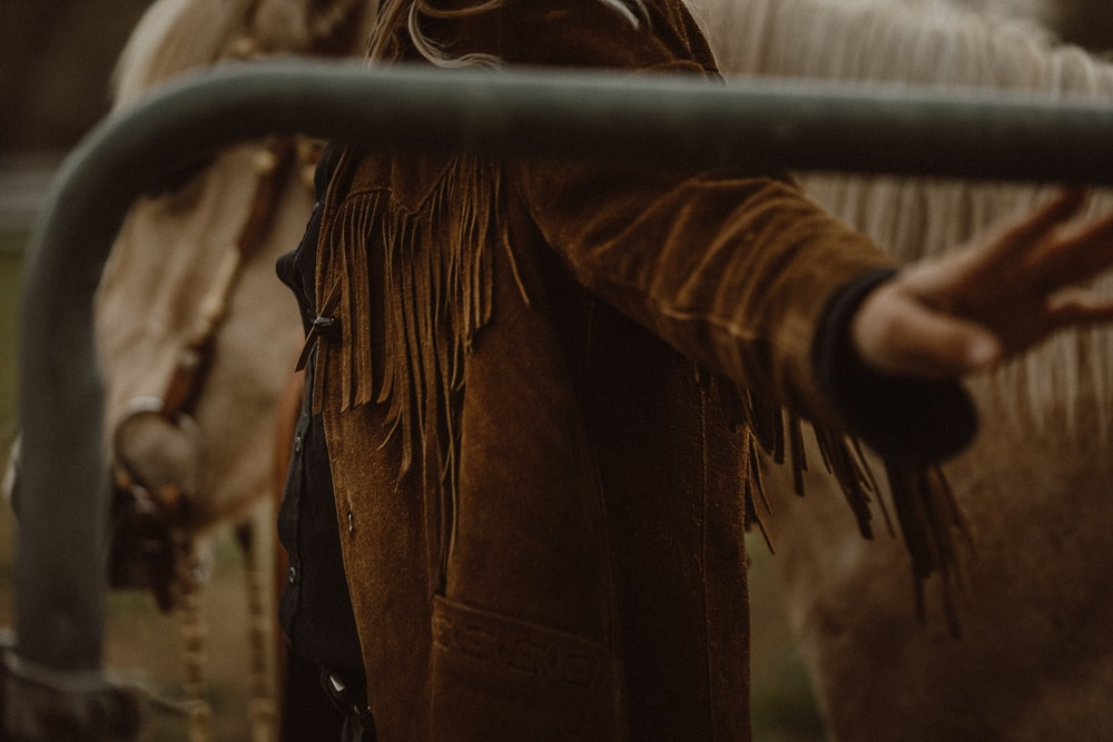 person in brown long sleeve shirt holding brown rope