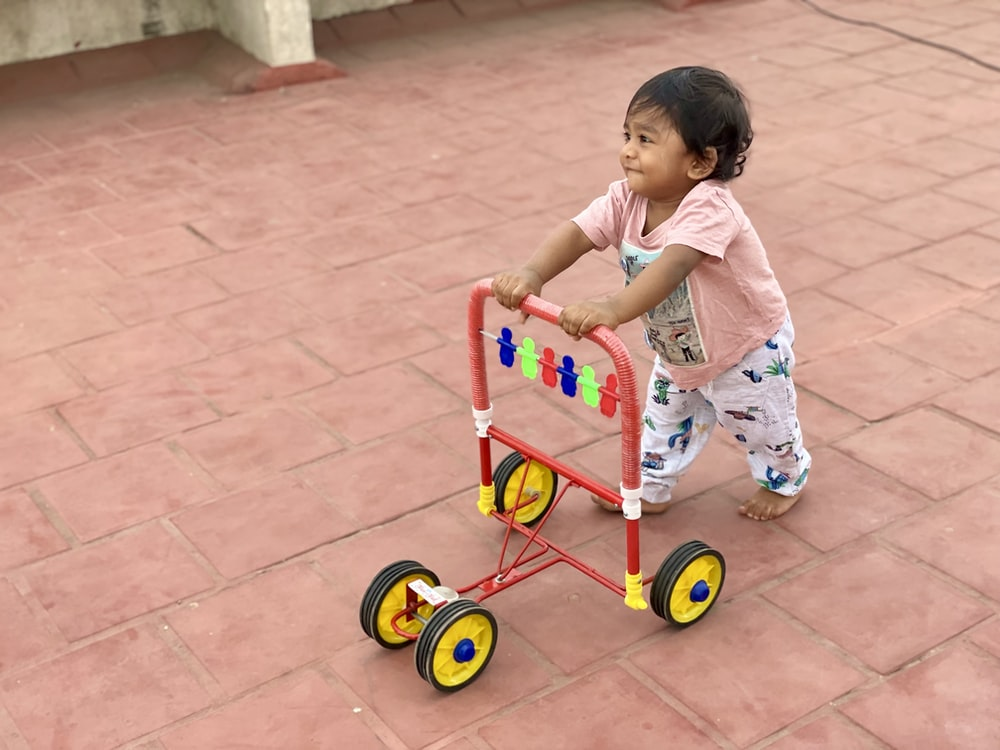 girl in white and pink floral dress riding red and yellow trike