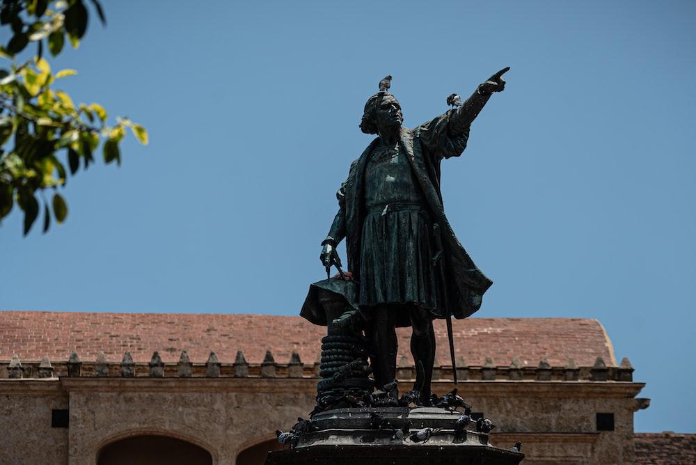 black statue of man holding yellow umbrella