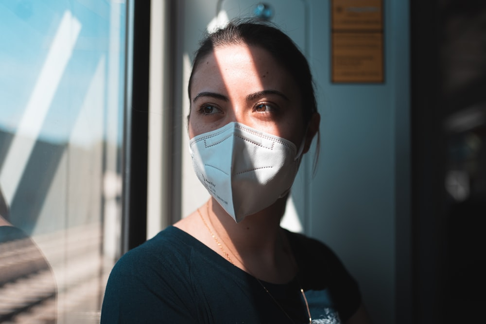woman in black v neck shirt with white face mask