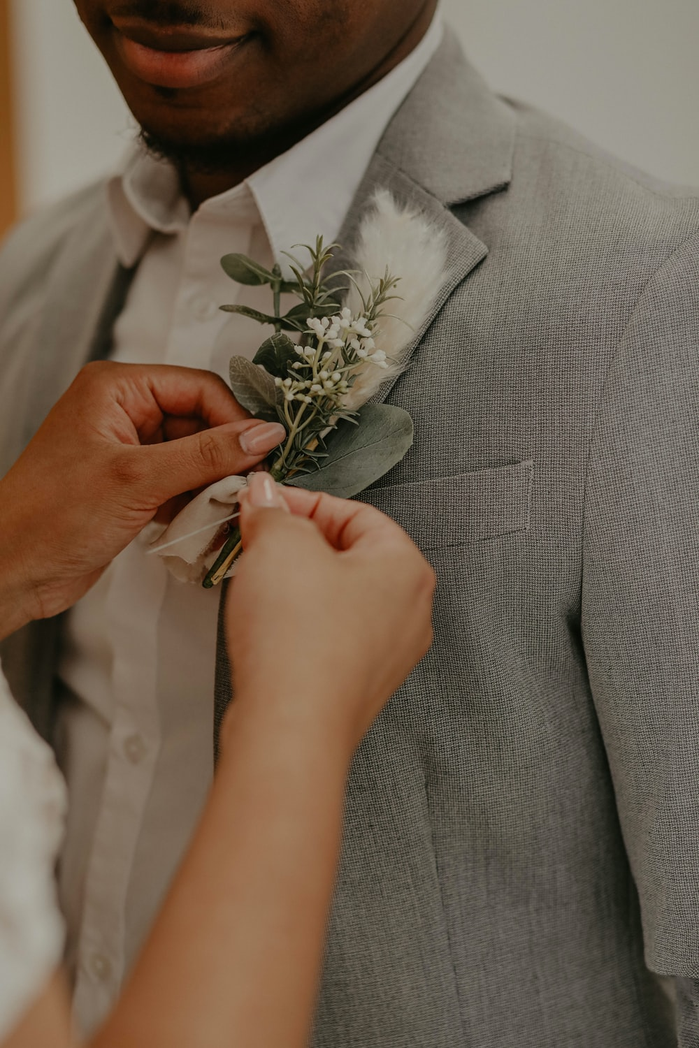 man in gray suit holding white rose