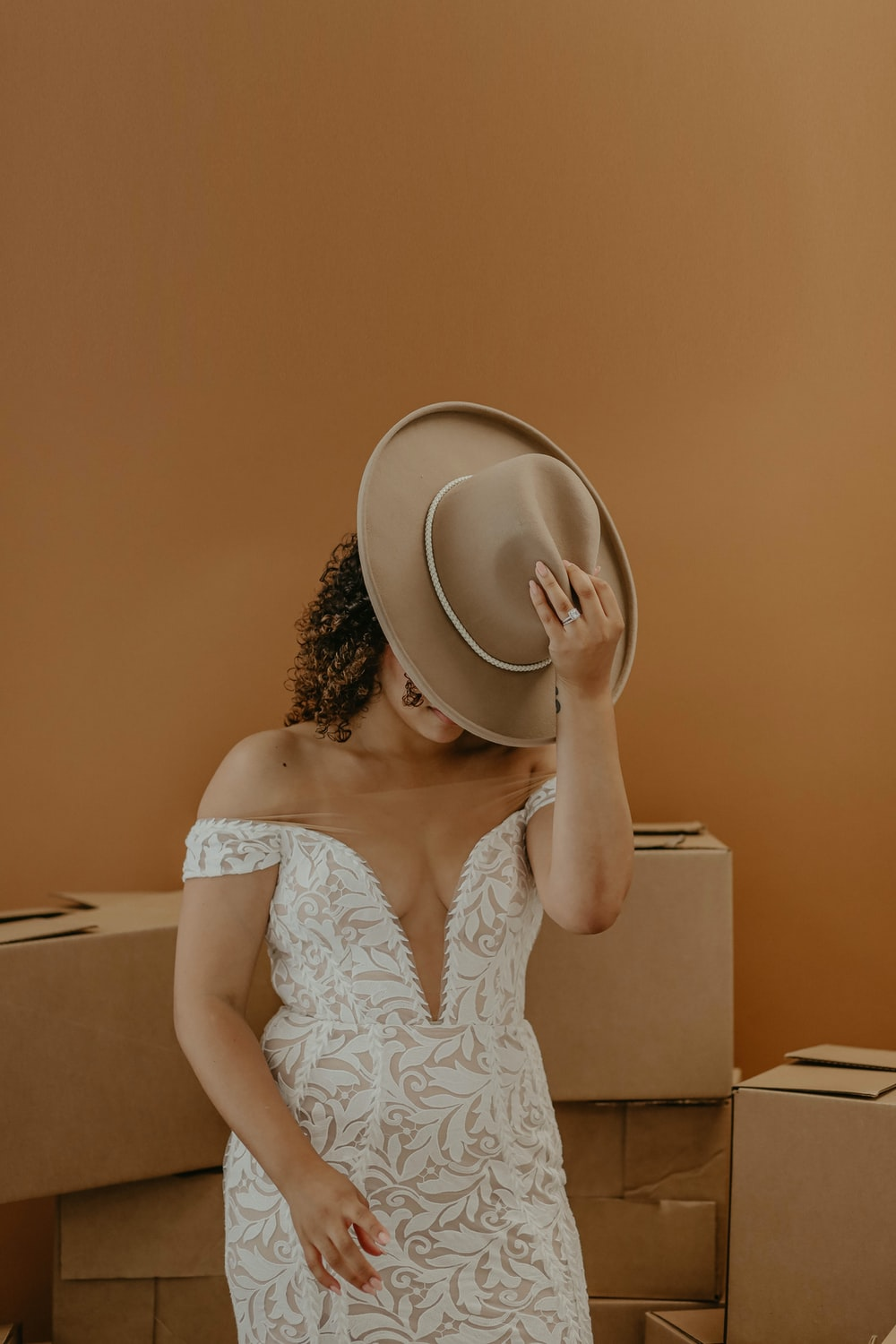 woman in white floral tank top holding brown hat