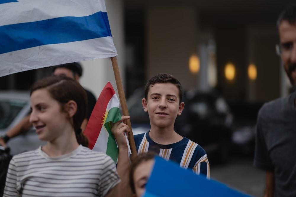man in white crew neck shirt holding blue flag