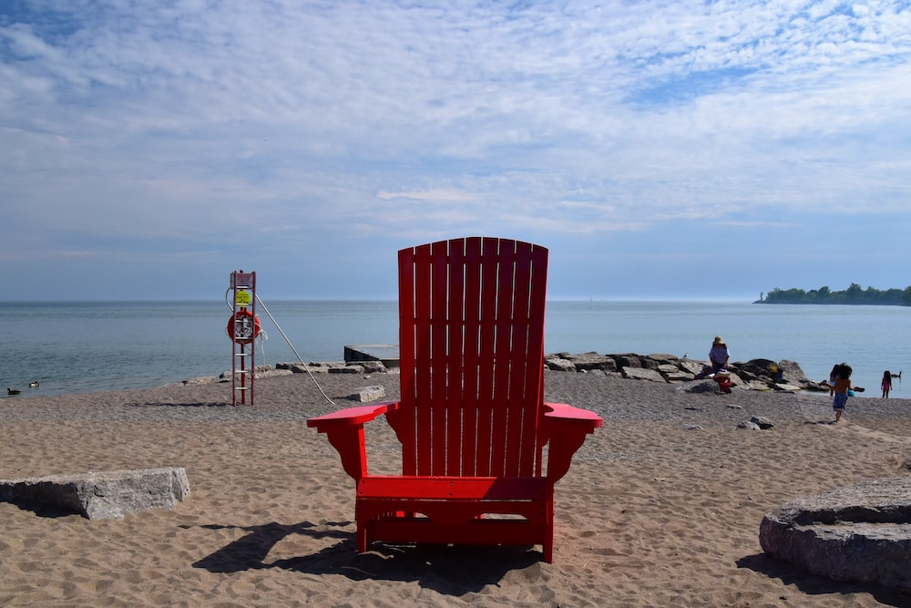 red wooden armchair on beach shore during daytime