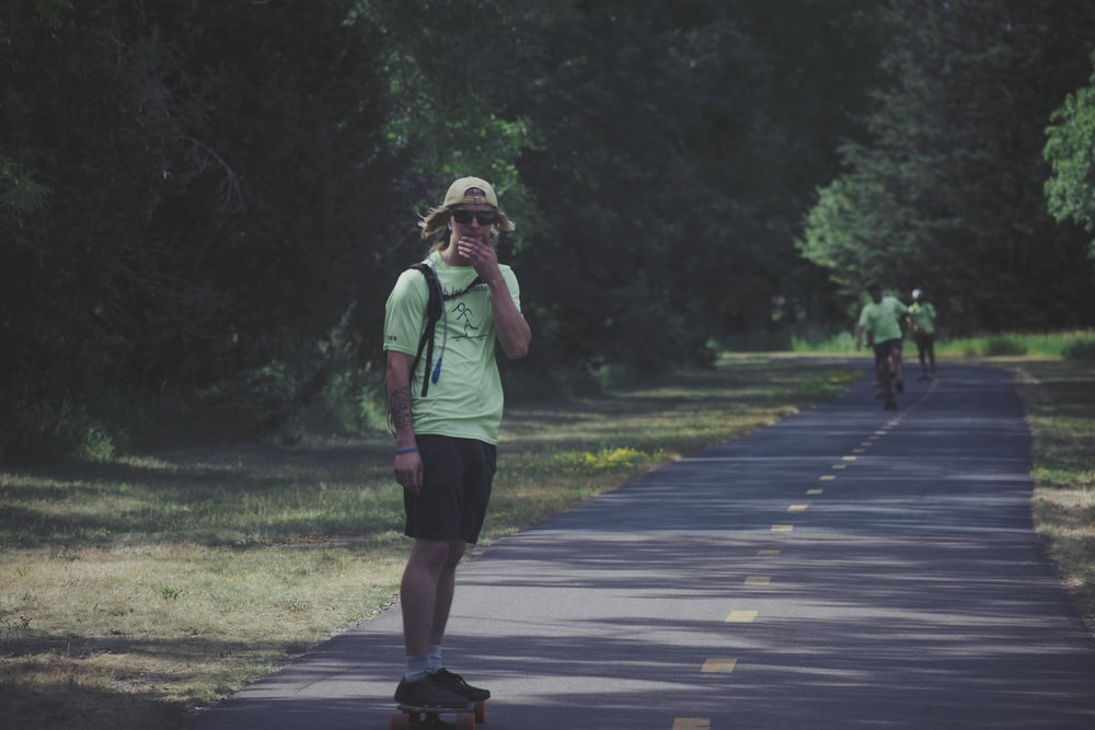 woman in green shirt and black shorts walking on gray asphalt road during daytime