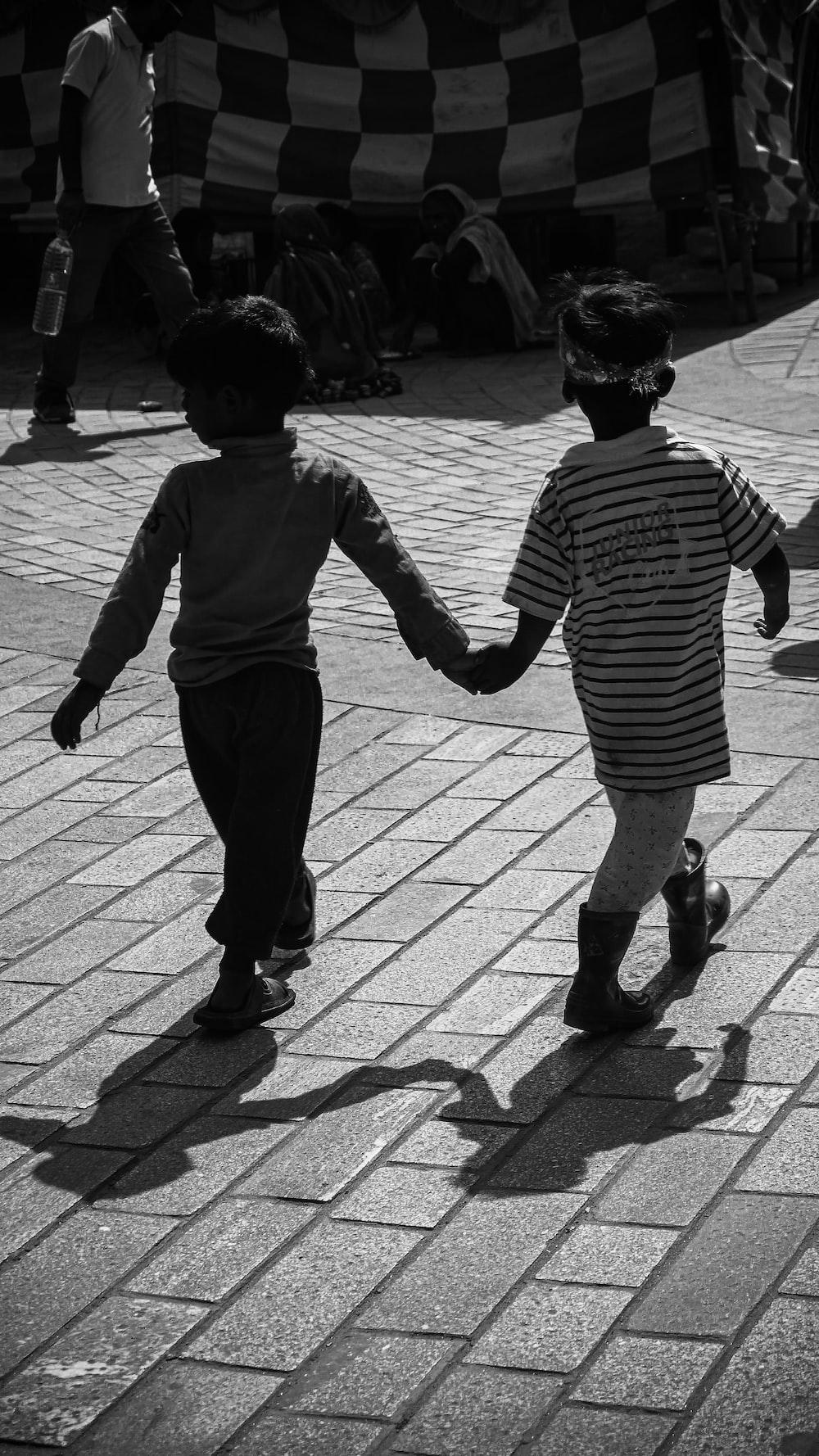 boy in black and white striped long sleeve shirt walking on sidewalk during daytime