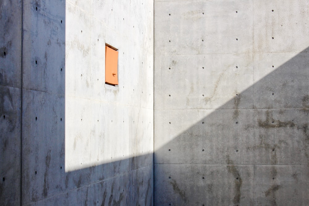 orange and white sign on gray concrete wall