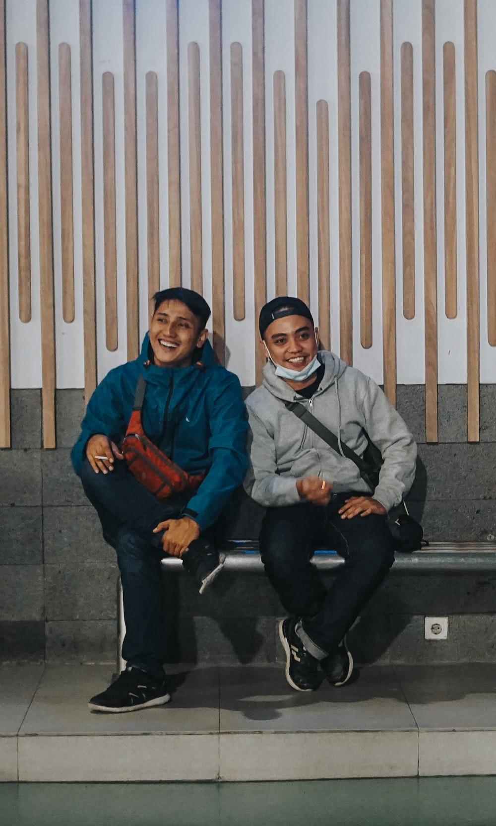 man in blue jacket sitting beside woman in gray jacket