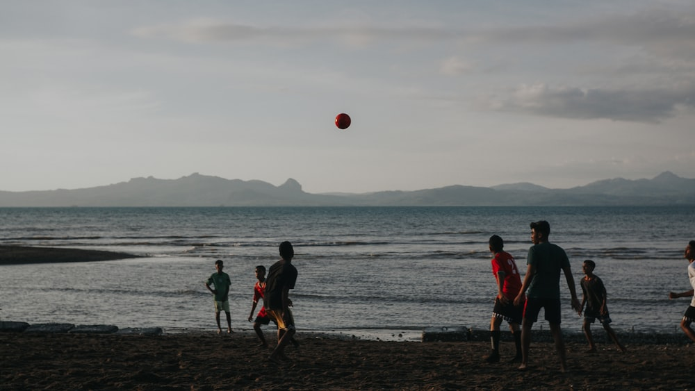 people playing soccer on beach during daytime