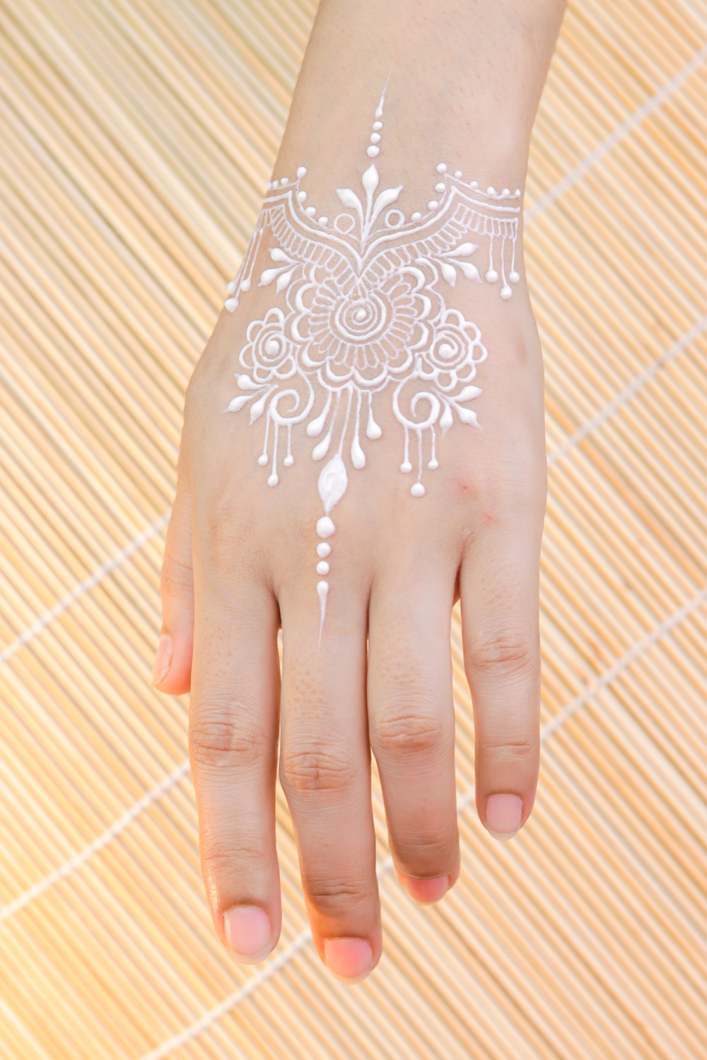 person with white and red floral hand tattoo