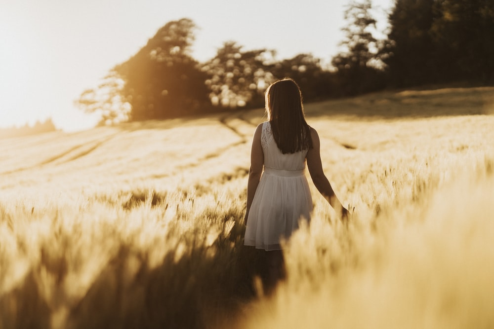 woman in white dress standing on brown grass field during daytime