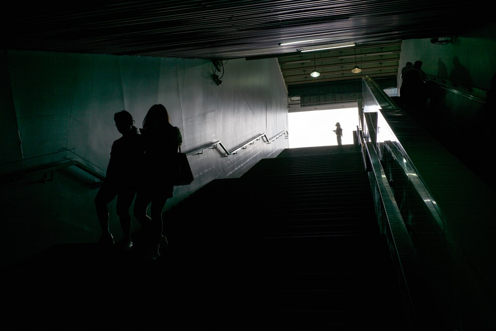 silhouette of 2 person walking on stairs