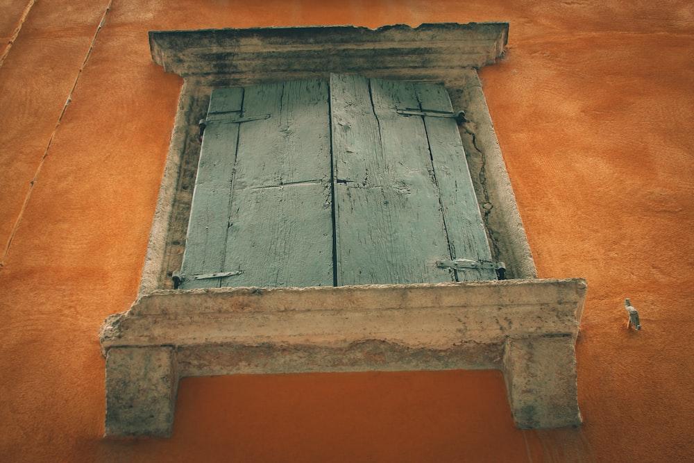 gray wooden door on orange wall