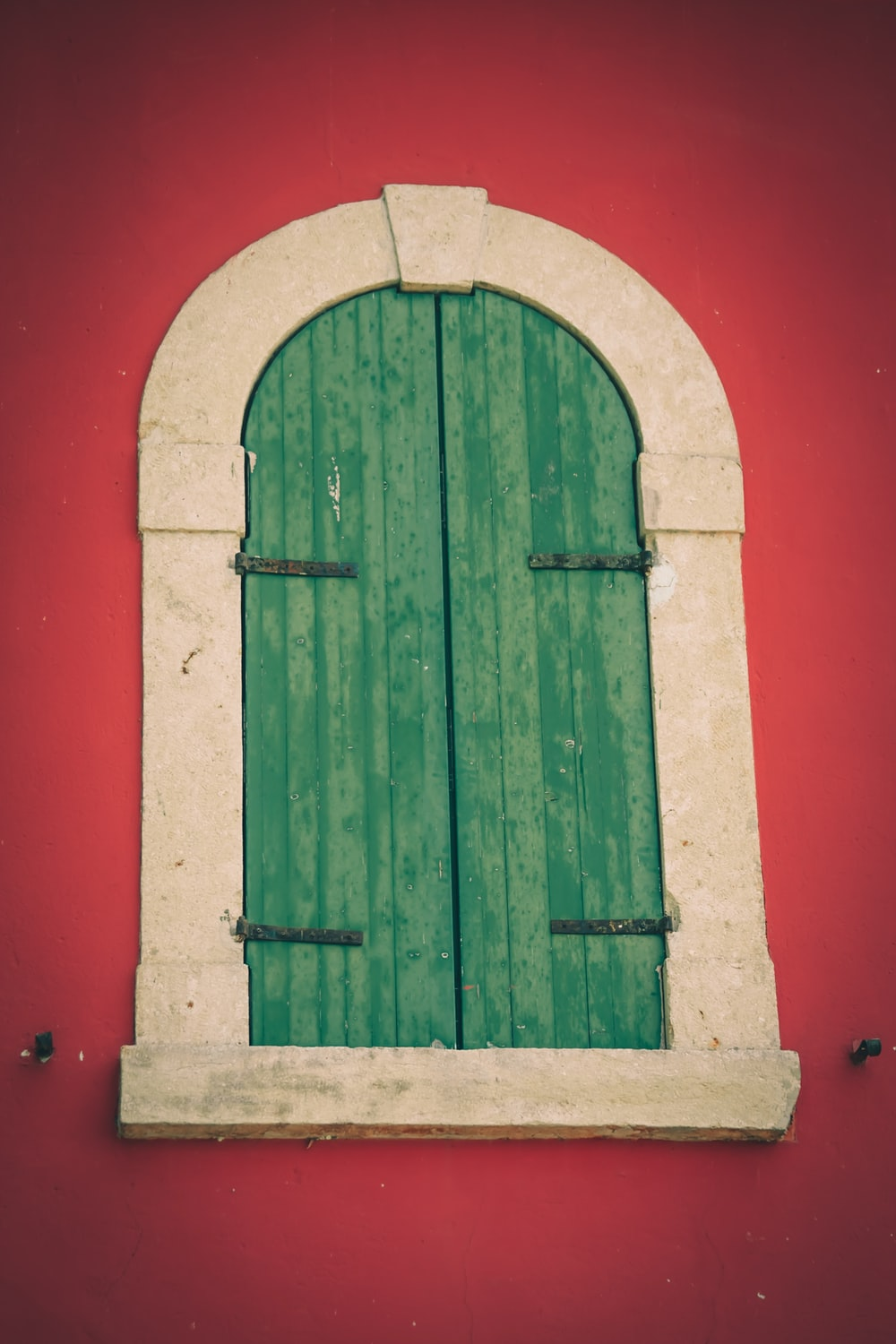 green wooden window on red wall