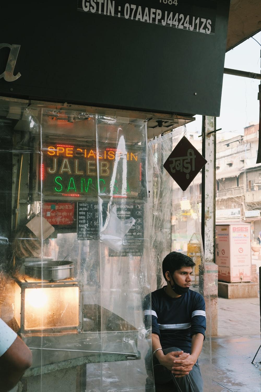 man in black jacket standing beside glass window