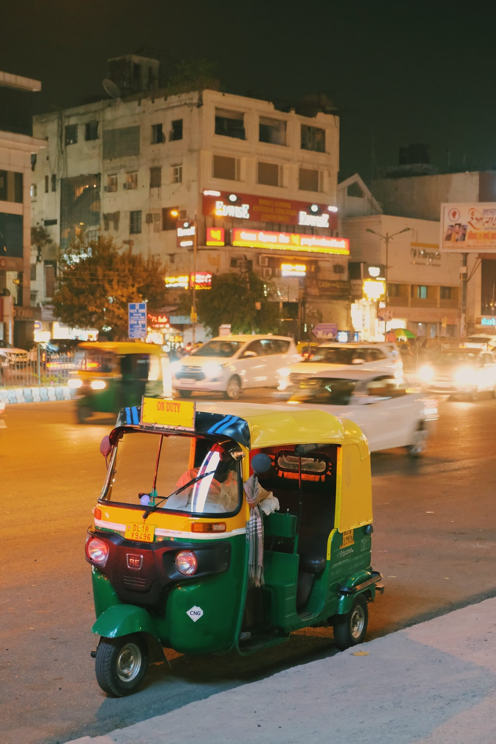 blue and yellow auto rickshaw on road during night time