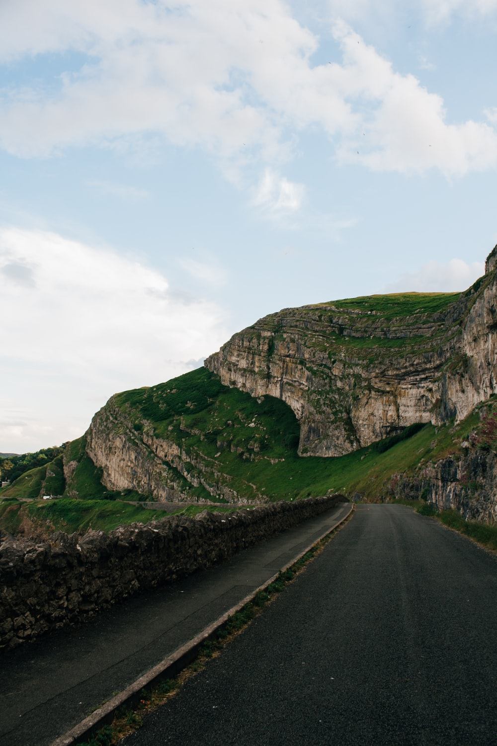 gray asphalt road beside green and brown mountain under white cloudy sky during daytime
