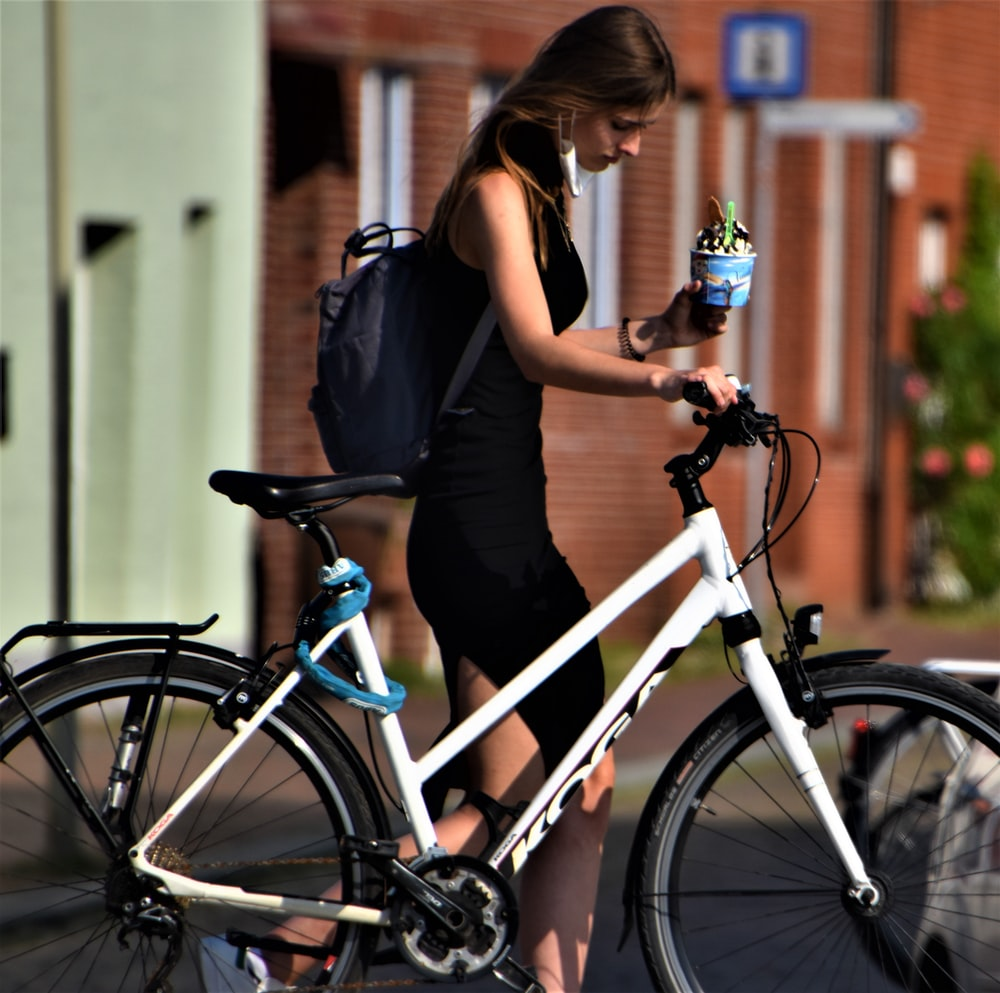 woman in black sleeveless dress standing beside white and blue bicycle during daytime