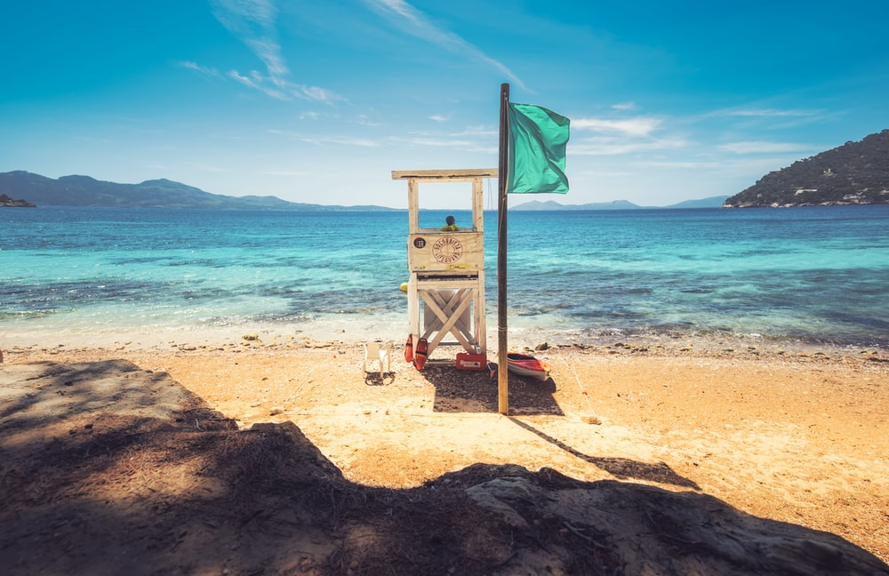 brown wooden lifeguard tower on beach shore during daytime