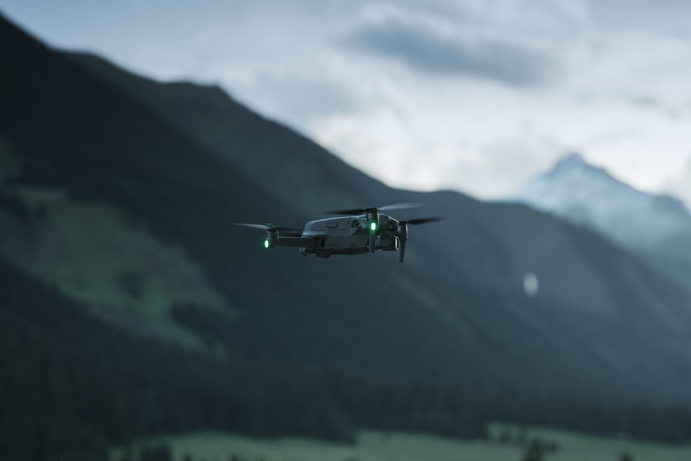 green and white drone flying over green mountain during daytime